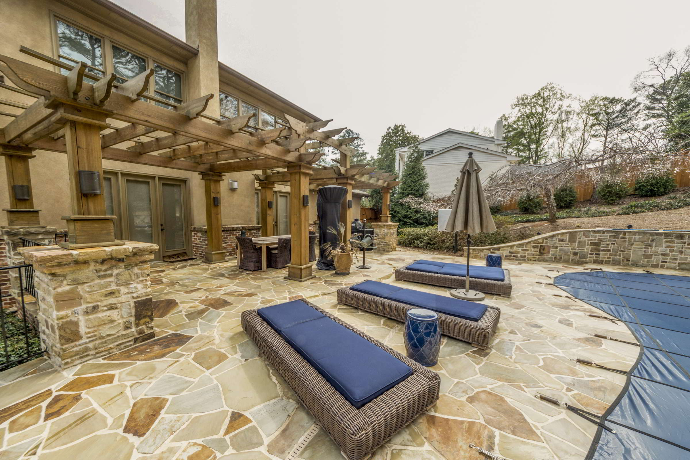 wooden pergola over stone poolside deck patio with blue lounge chairs and umbrella