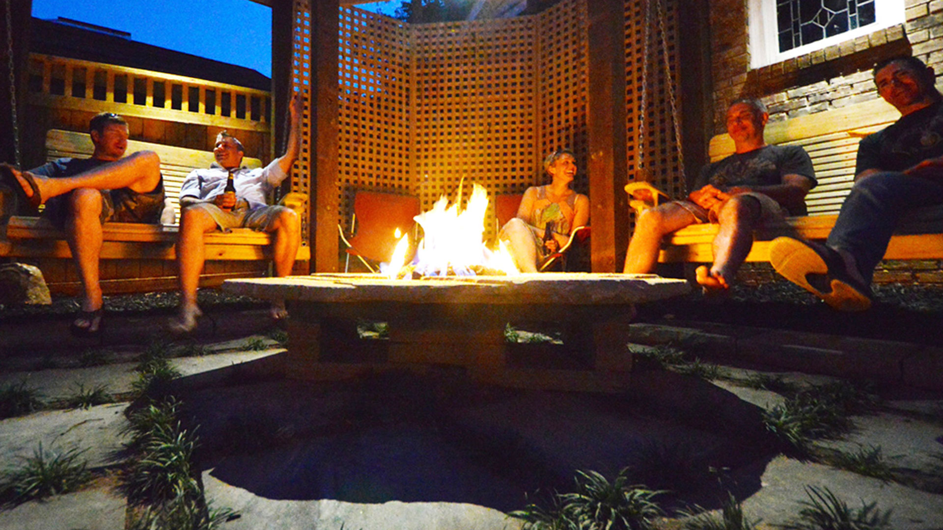 people sitting around outdoor living space with fire pit and wooden swings