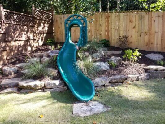 green plastic slide in fenced in backyard