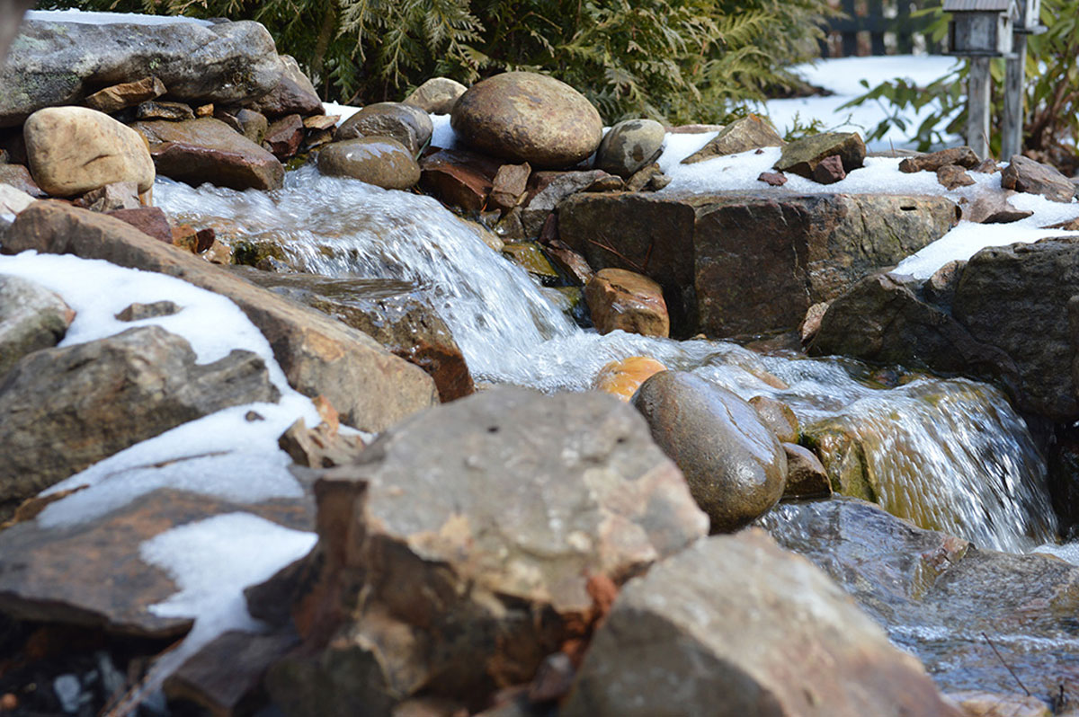 stone landscape water fall feature covered in snow