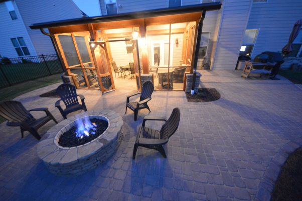 backyard outdoor chairs around stone fire pit and backyard screened-in porch