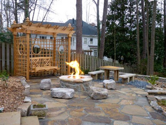 small backyard wooden pergola with swing by stone fire pit and stone bench and table