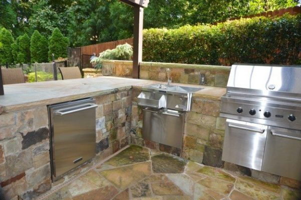 stone outdoor kitchen with steel grill, sink, and refrigerator in landscape backyard