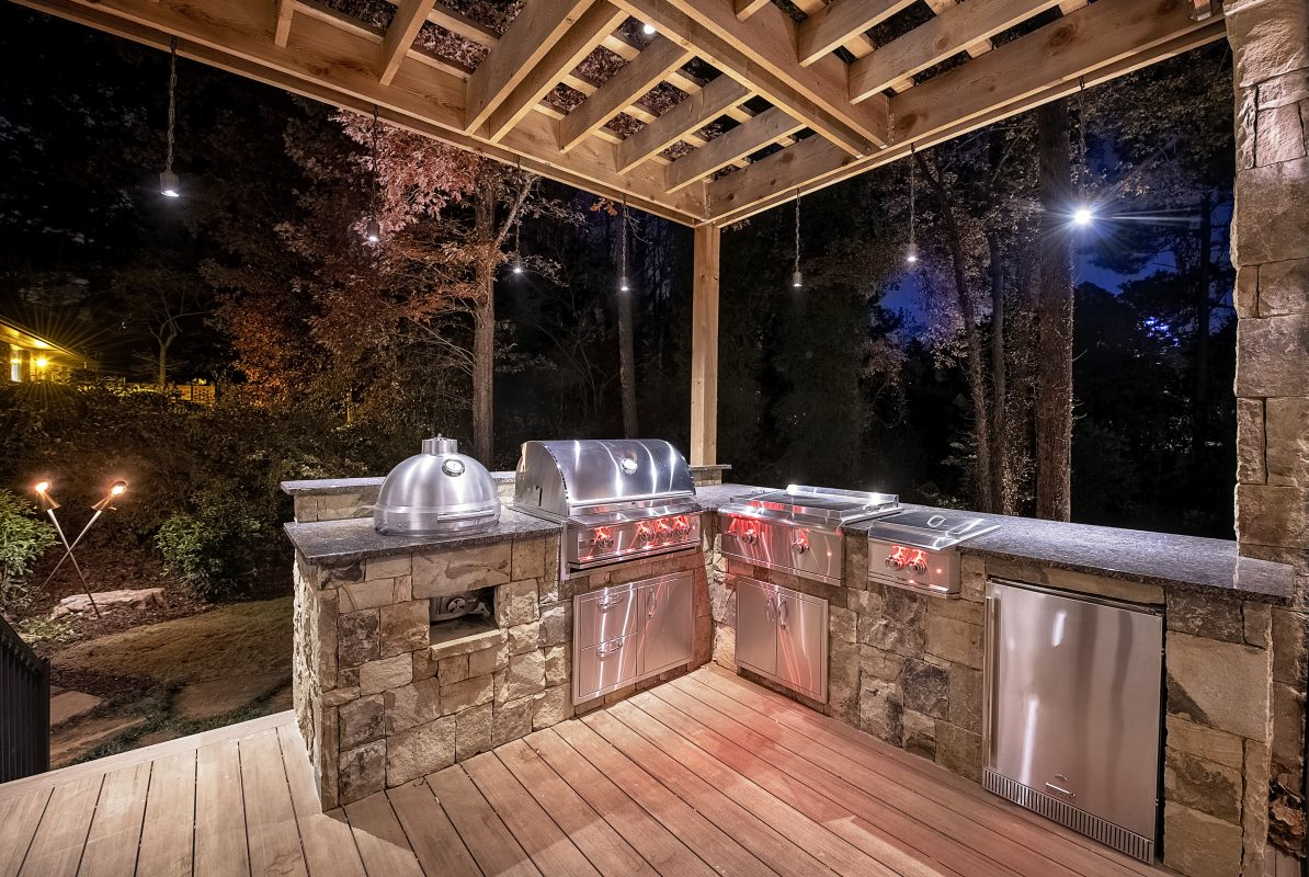 outdoor kitchen and grill on wood deck with pergola and outdoor lighting