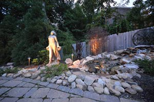 stonescaping and hardscaping with wooden fence and exterior lit statue
