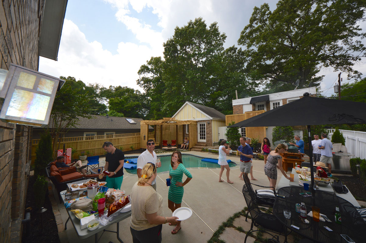 outdoor event on pool deck living space with tables of food and people grilling