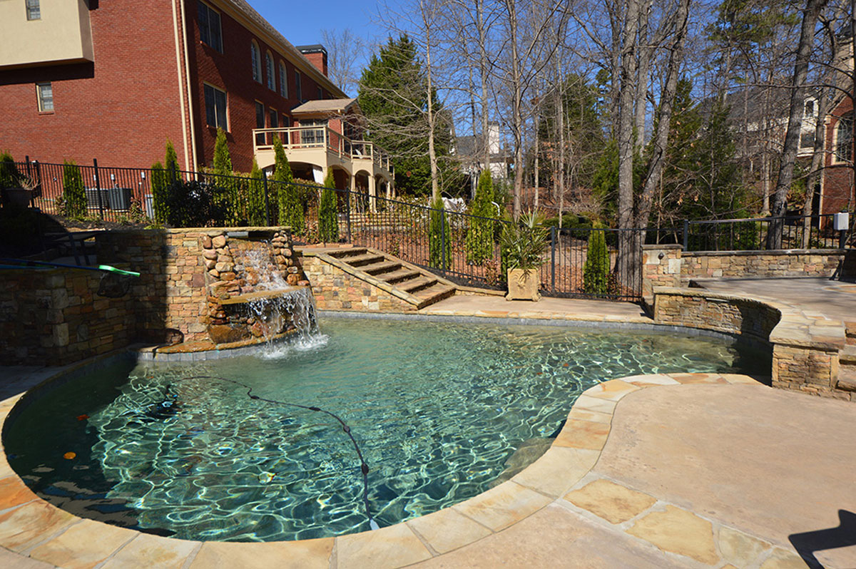 backyard stone pool with water fall feature, iron fence, and hardscaping