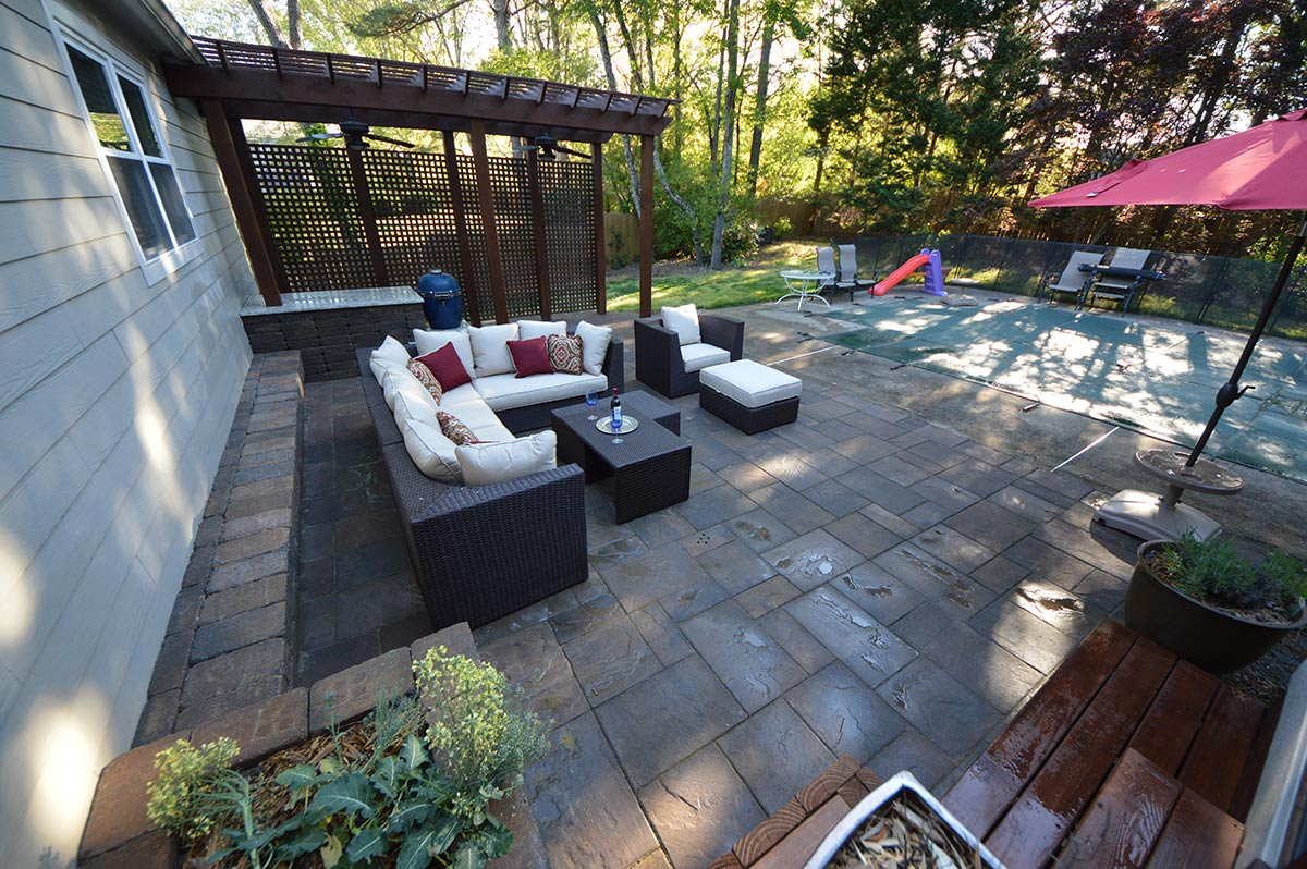 outdoor cushioned furniture on a family outdoor living space stone patio with pergola, grill and outdoor covered pool