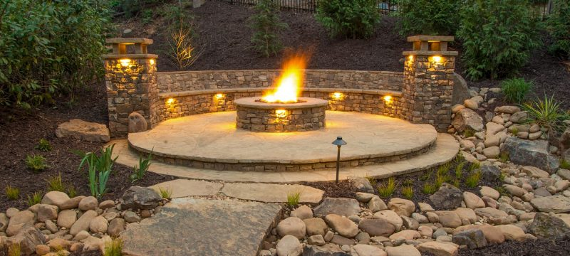 outdoor fire feature on hardscape outdoor living space with outdoor pathway and surface lighting