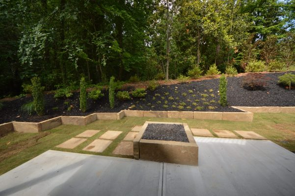 new landscape makeover with stone walkway, softscaping, and mulched backyard