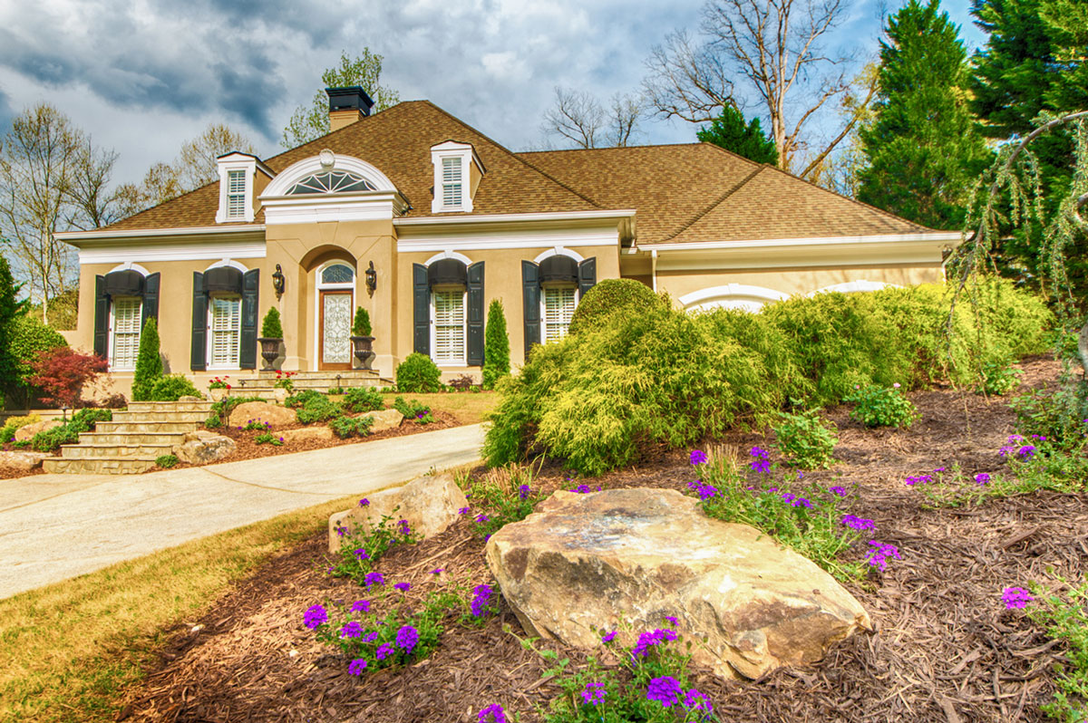 front yard landscape with stones, bushes, and purple flowers