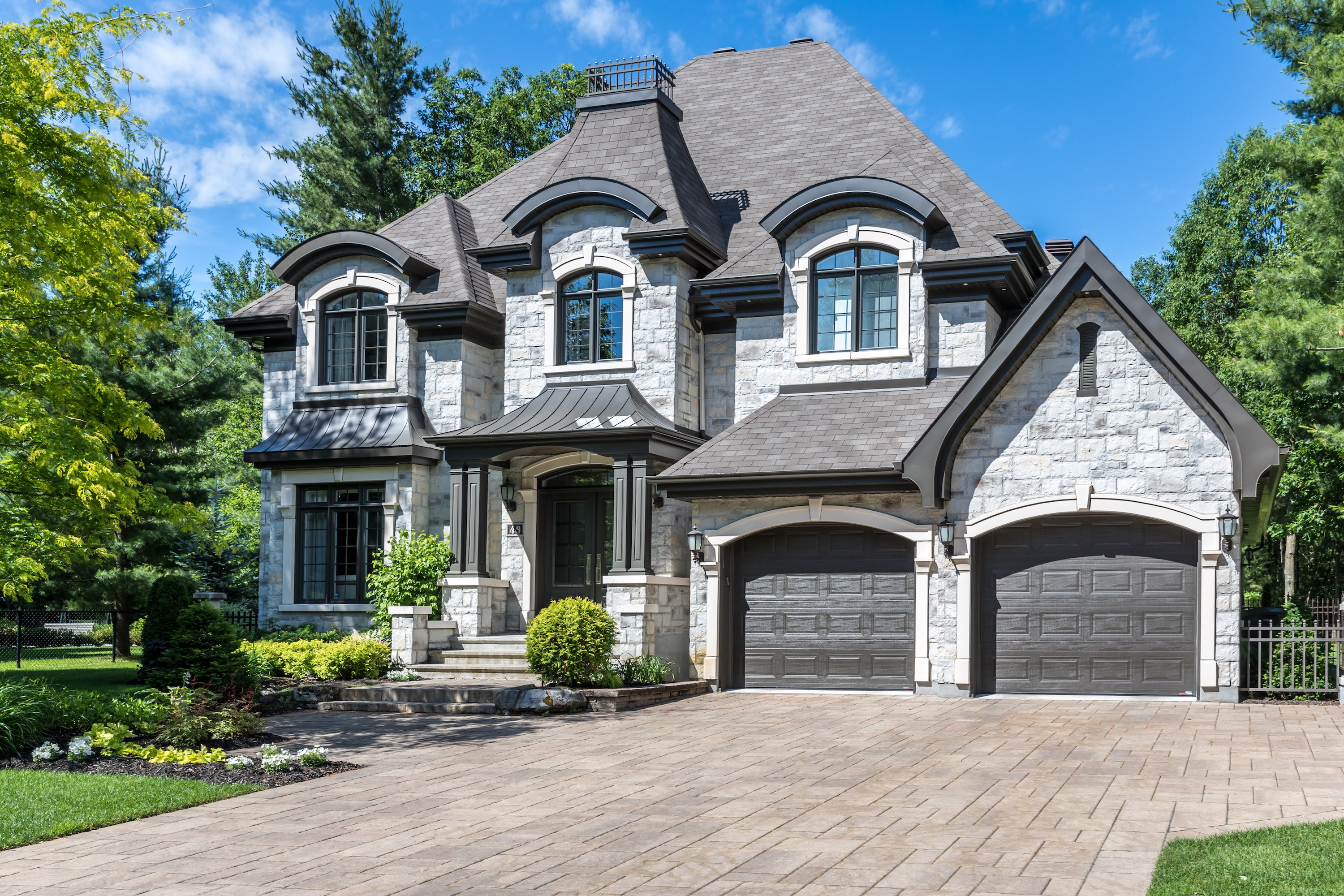 luxury stone house with paver driveway and two car garage