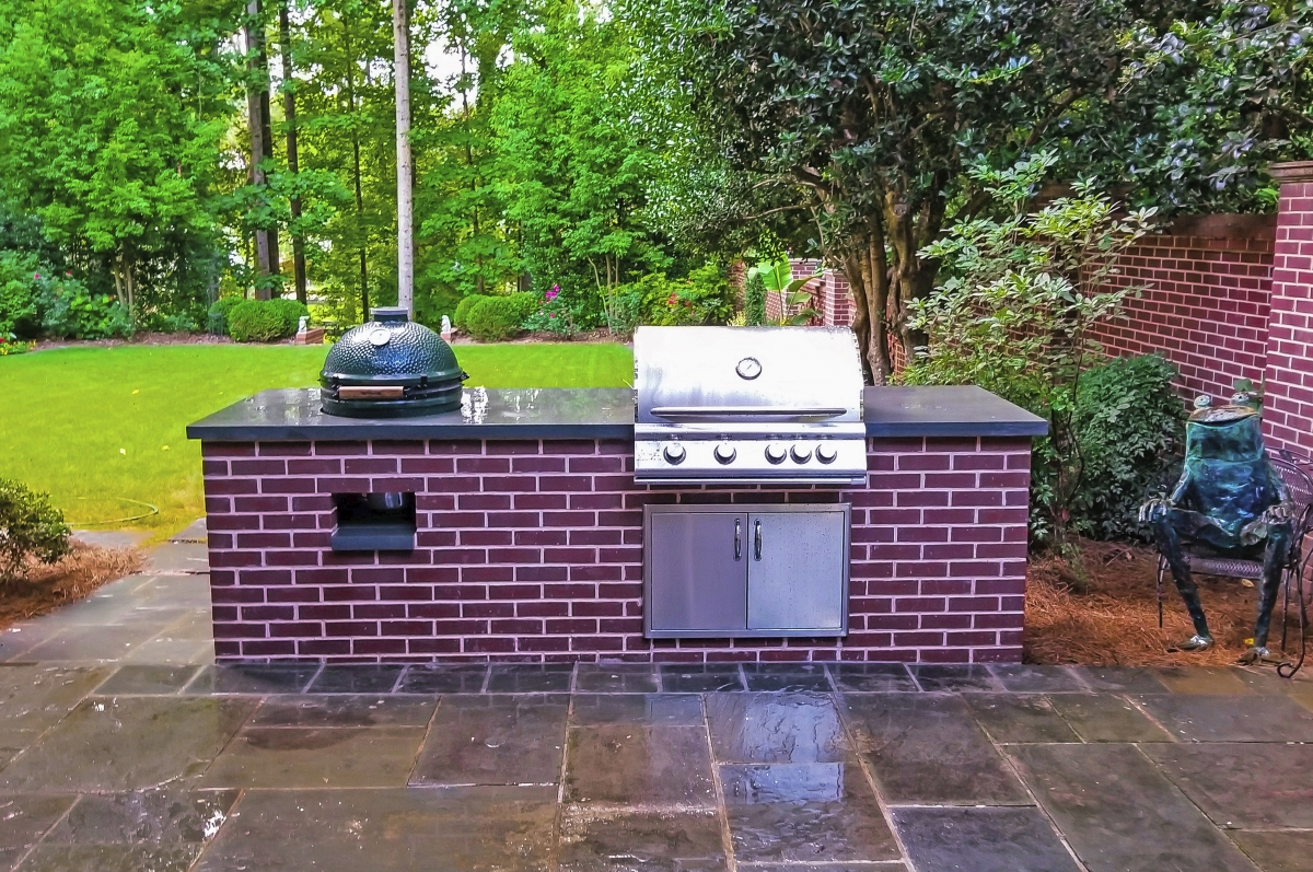 brick outdoor kitchen with grill and green smoker in backyard next to frog statue
