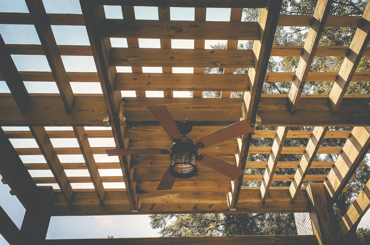 ceiling fan hanging from wooden outdoor pergola