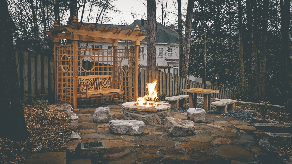 swing and pergola next to backyard fire pit in winter