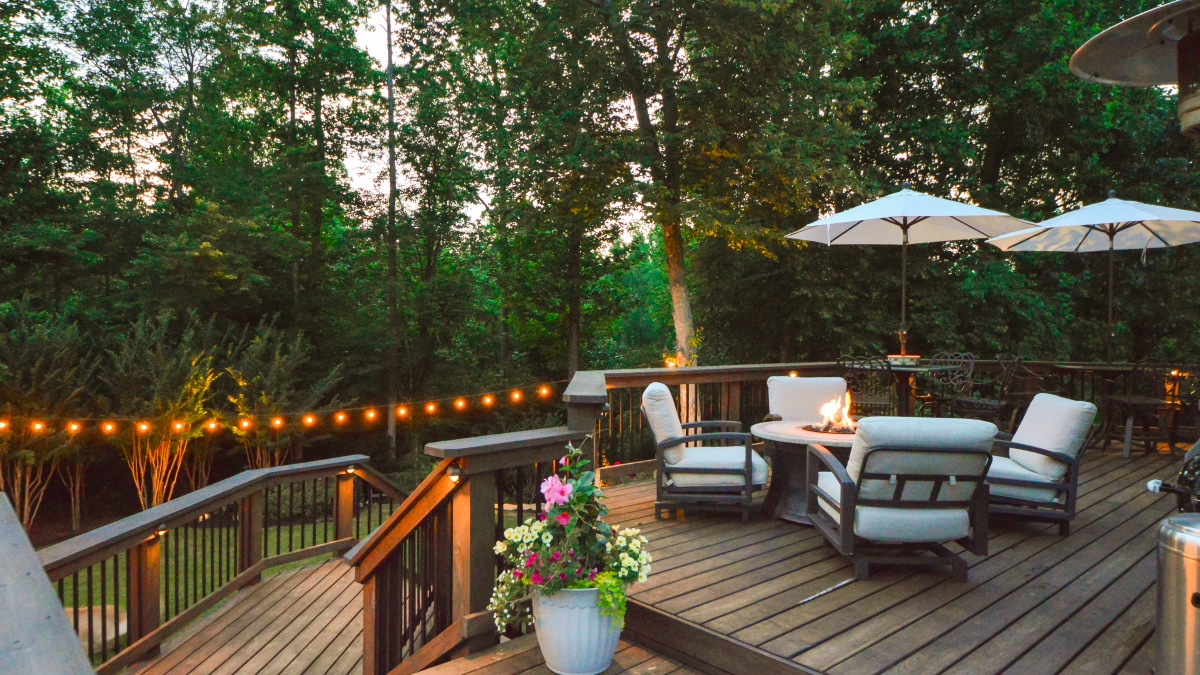 outdoor living space with fire pit, cushioned outdoor chairs, umbrellas, and outdoor hanging string lights