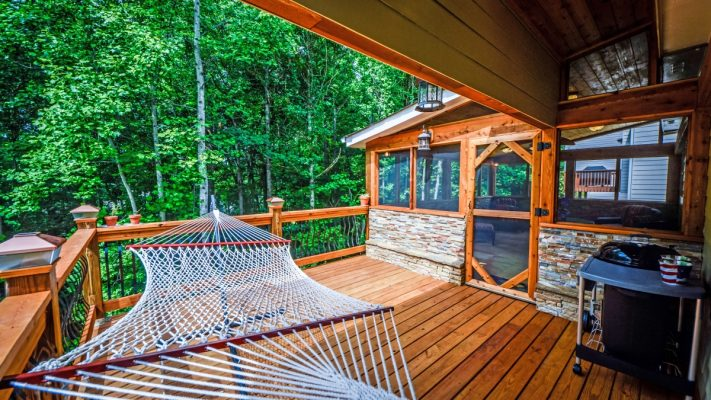 screened-in back porch with hammock on wood deck