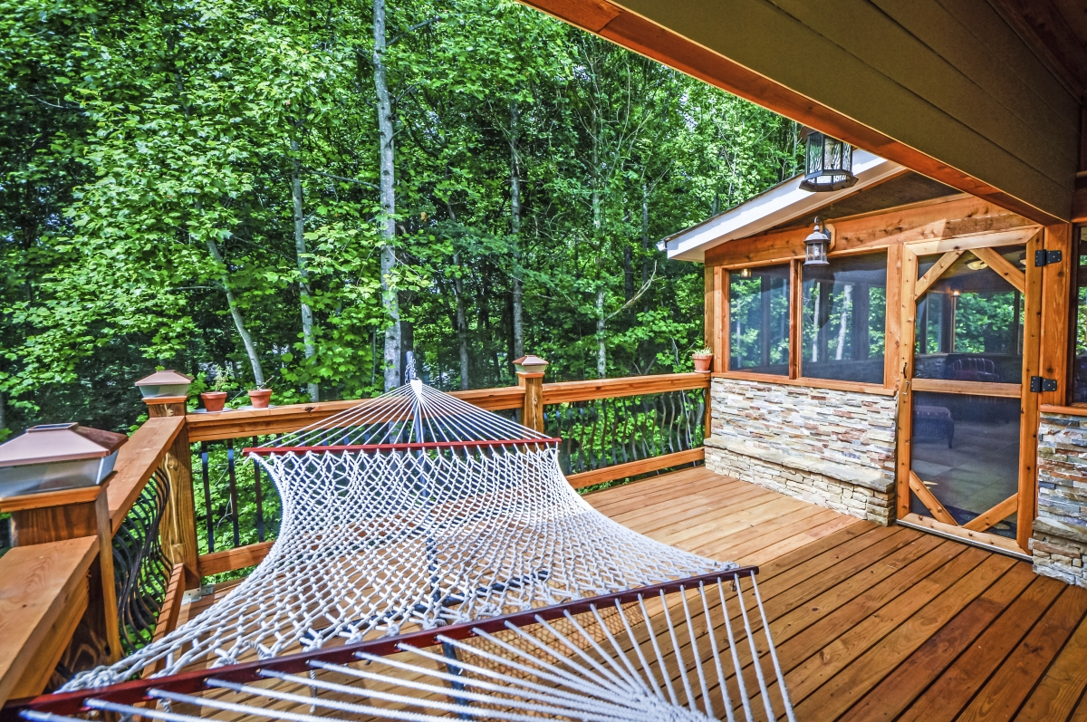 hammock on wood deck leading to screened-in back deck porch