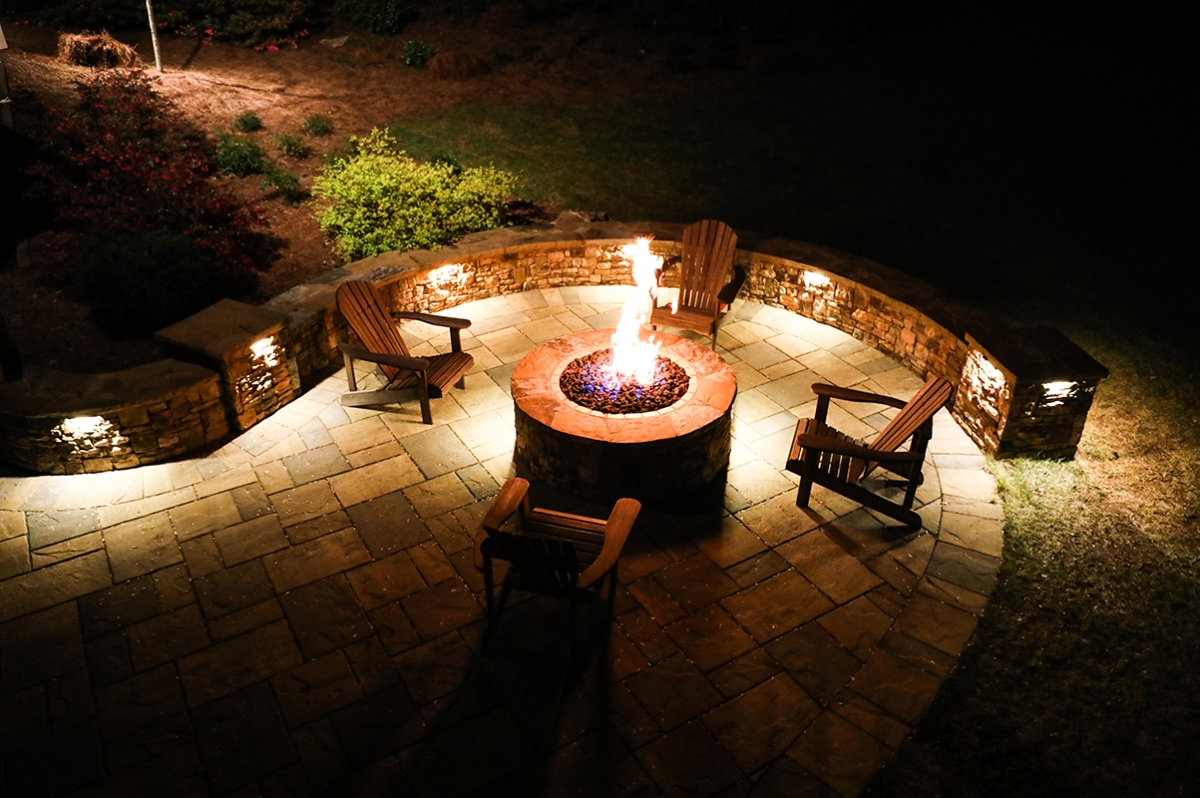 fire pit with wooden chairs and surface hardscape lighting at night
