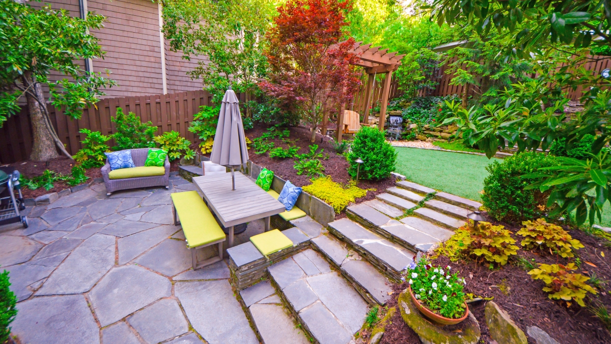 stone backyard patio living space with colorful landscaping