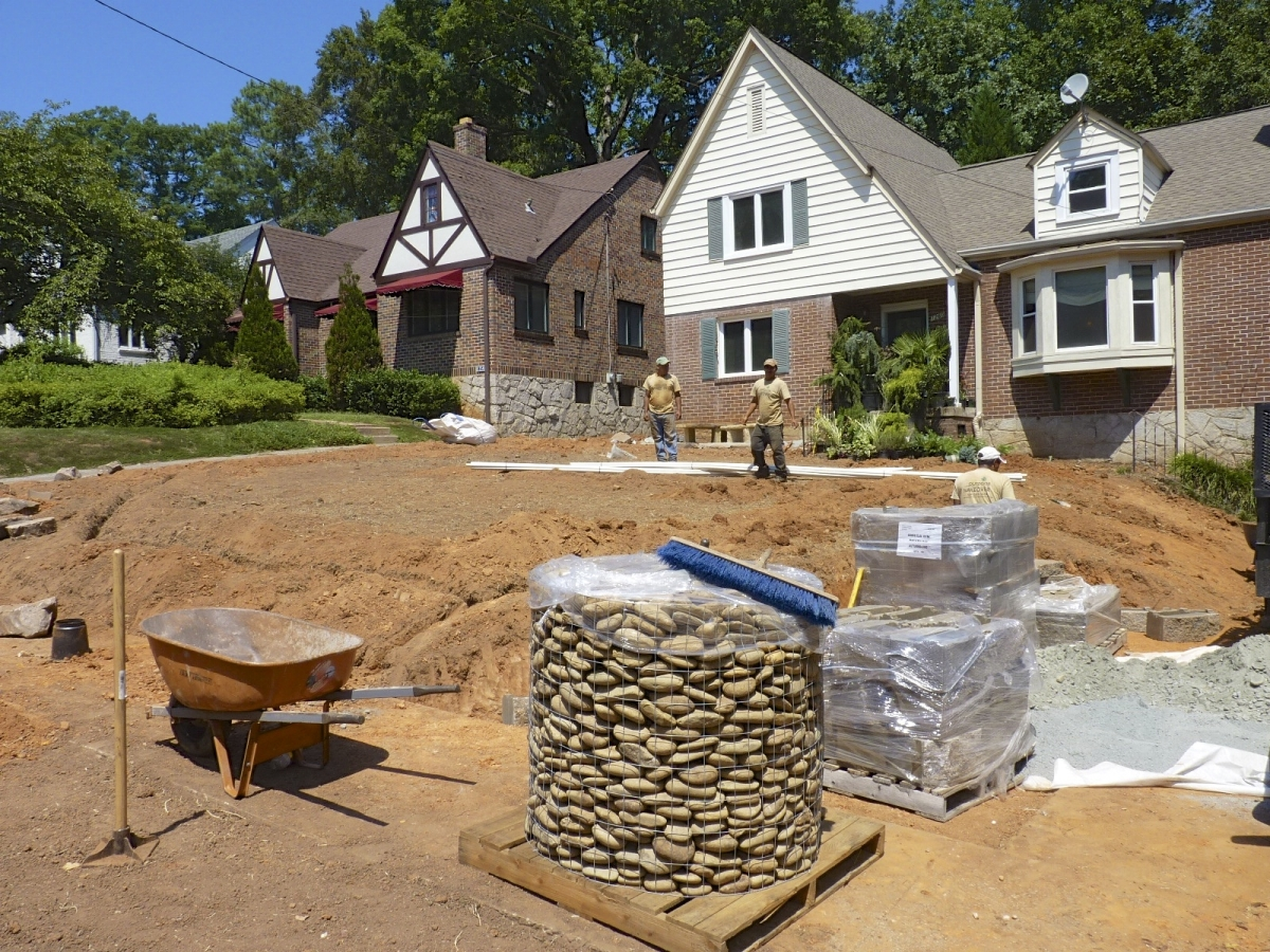 white and brick home undergoing landscape overhaul and construction