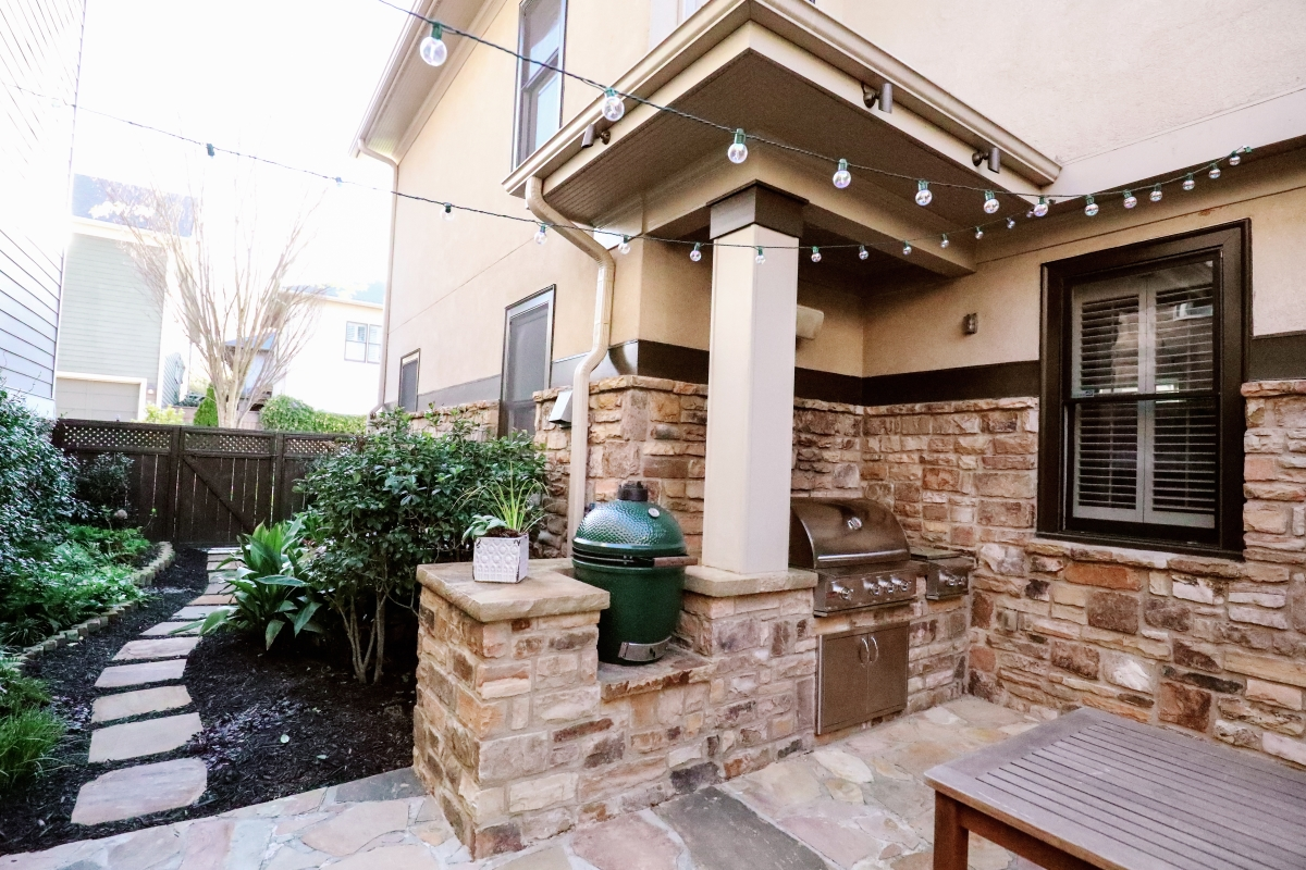 outdoor kitchen and living space with steel grill and big green egg