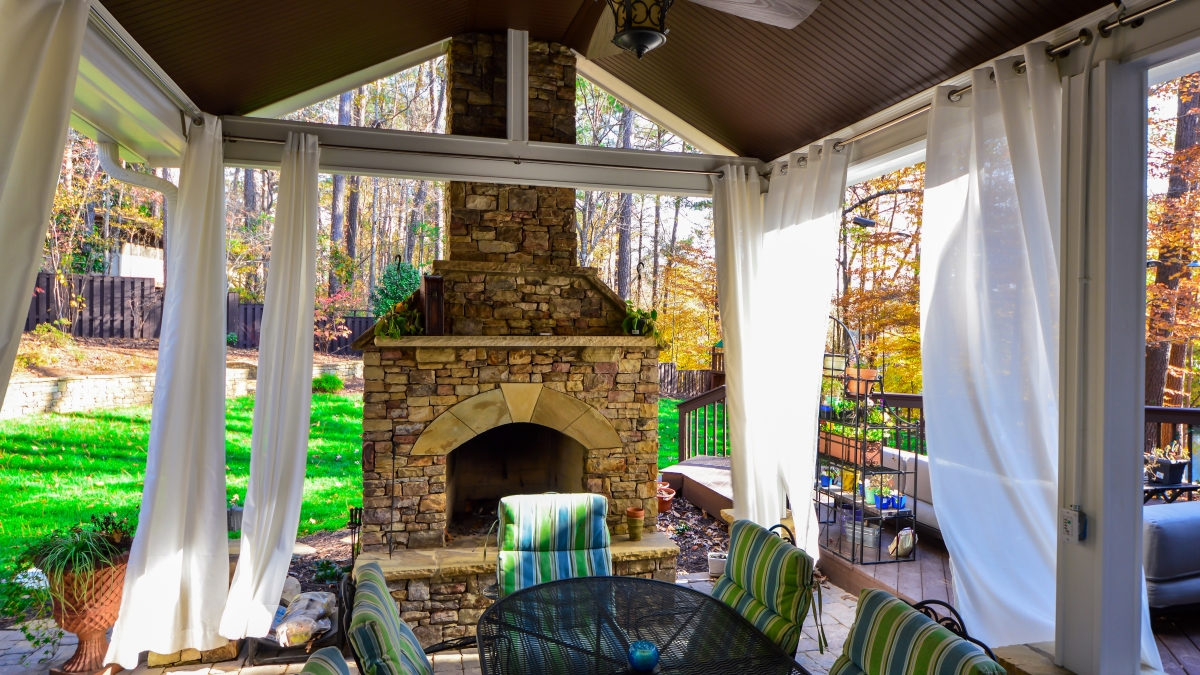 outdoor living room with white curtains and stone fire place next to outdoor table set