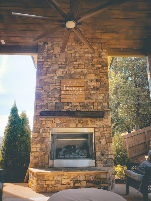 large ceiling fan above stone fire place in outdoor living room