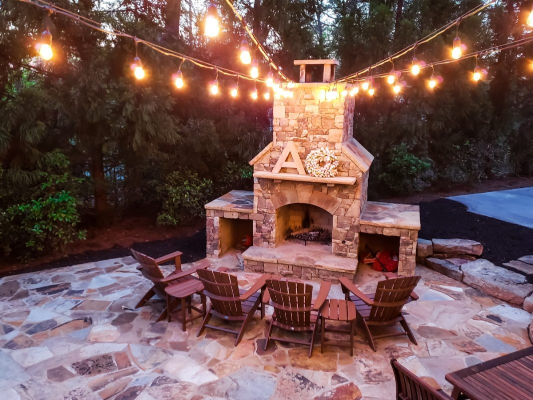 outdoor fireplace with string lights and seating
