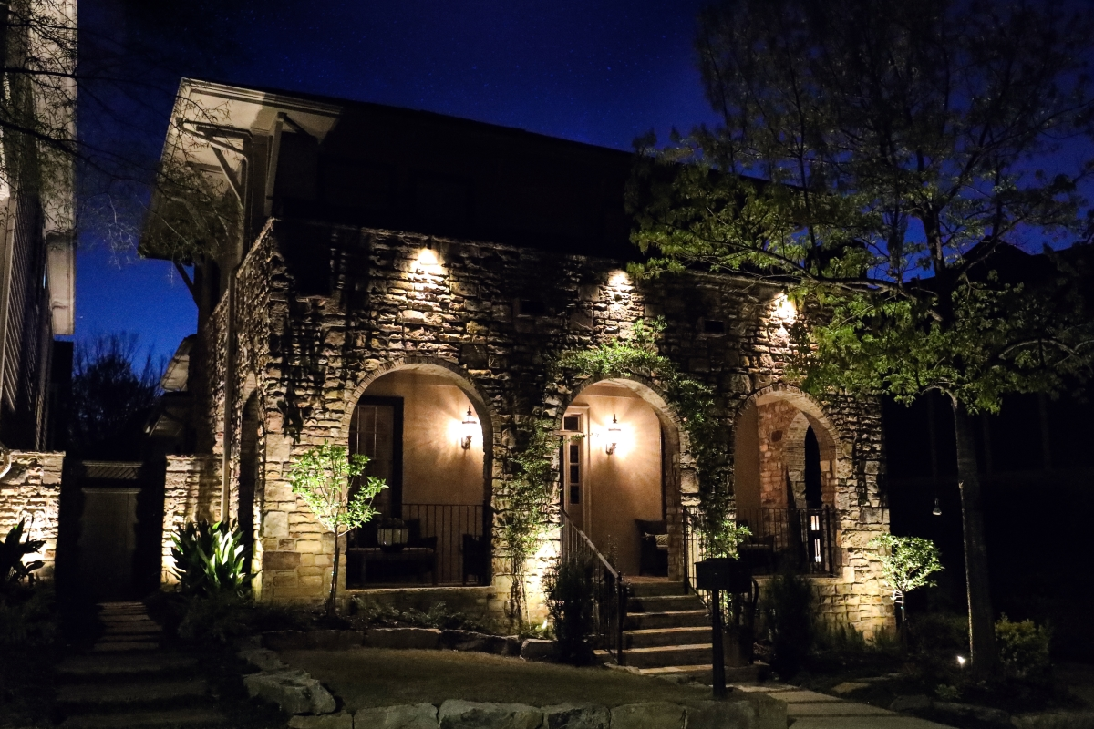 stone house with exterior surface lighting and front porch