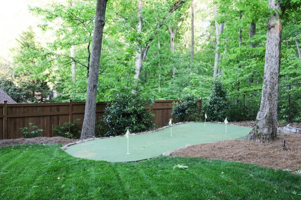 backyard putting green surrounded by short and tall trees