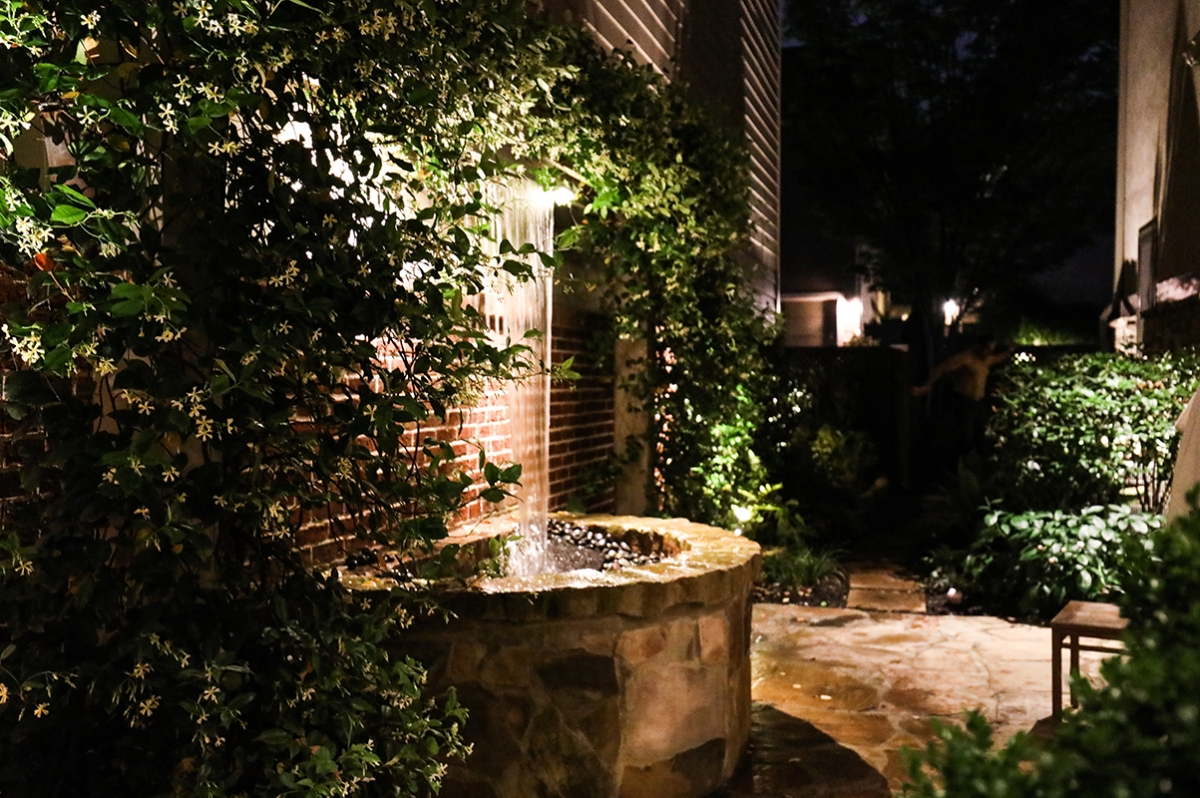 water fountain with vines growing in backyard living area