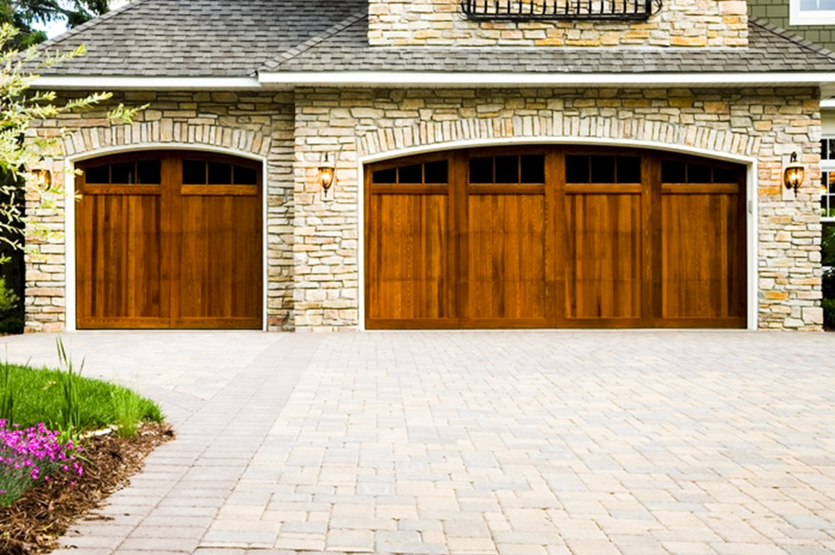 paver driveway with wooden garage door on stone house