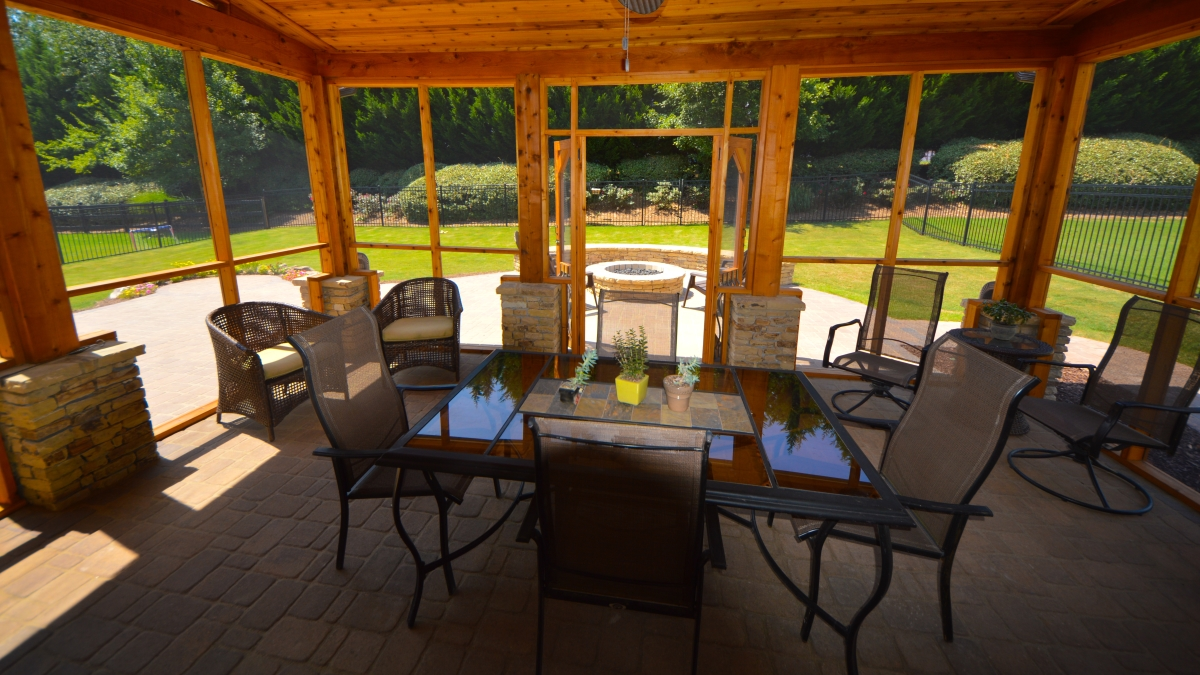 wooden screened-in porch with dining table and chairs