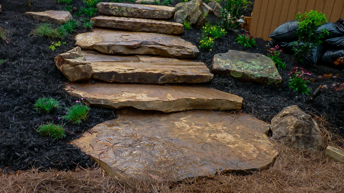 backyard stone steps with yellow, purple, and pink flowers