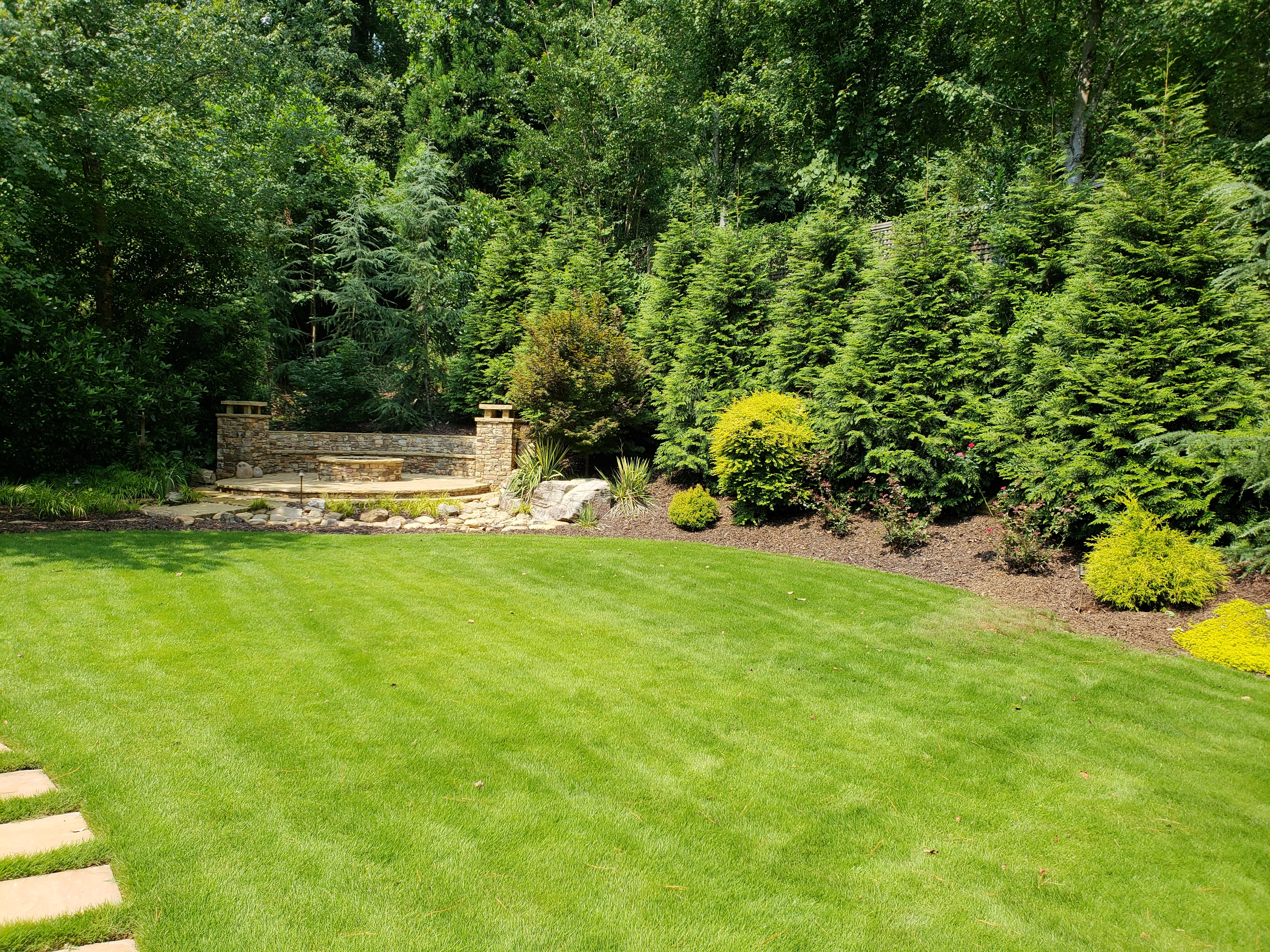 backyard landscaping with evergreen trees, stone patio, circular fire pit, and large grass yard