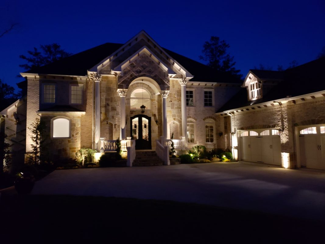 large stone house with outdoor lighting design at night