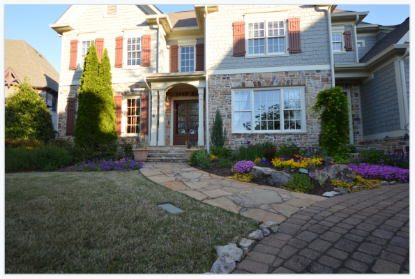 stone walkway leading to house with colorful flowers and hardscaping