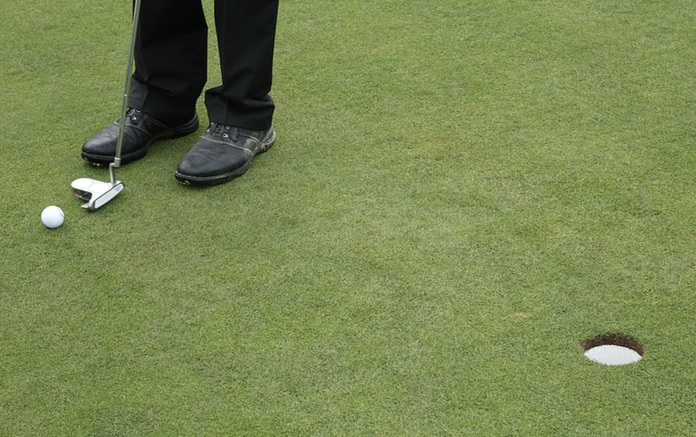 golfer with black pants and shoes lining up putt on backyard putting green