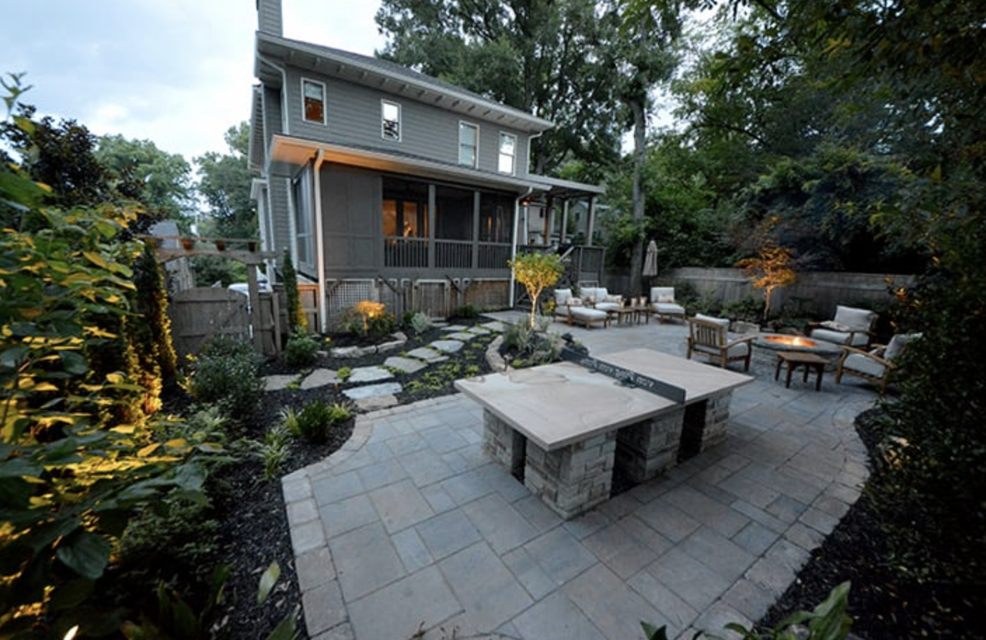 stone outdoor entertaining space in backyard landscape with table tennis, outdoor furniture, and outdoor fire pit