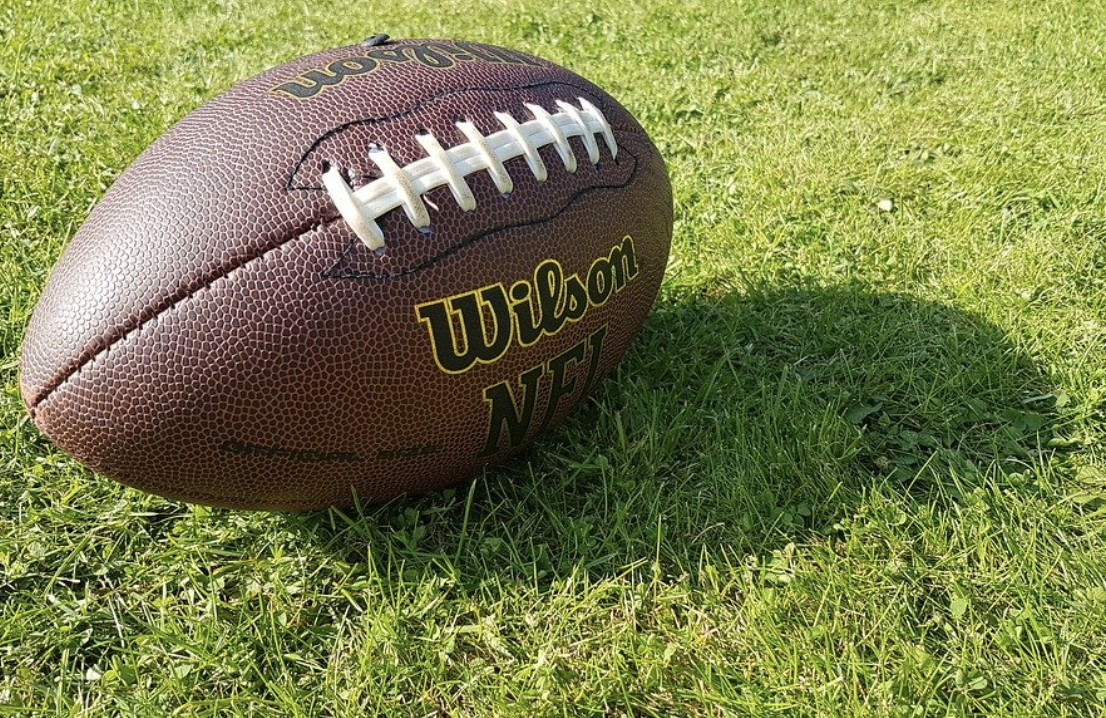 brown leather football on green grass in bright sunlight casting a shadow