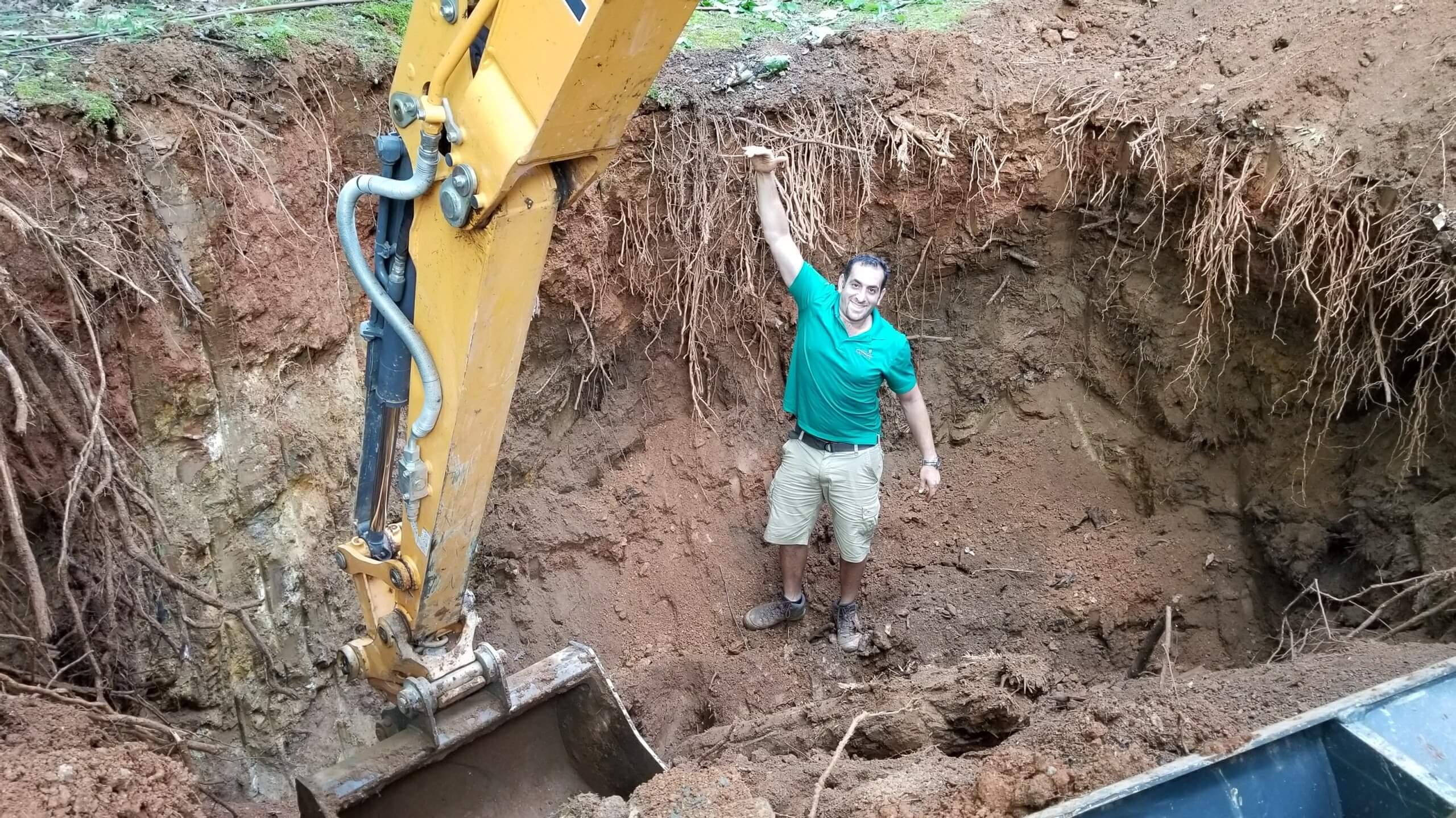 outdoor landscape construction designer showing depth of sink hole during repair