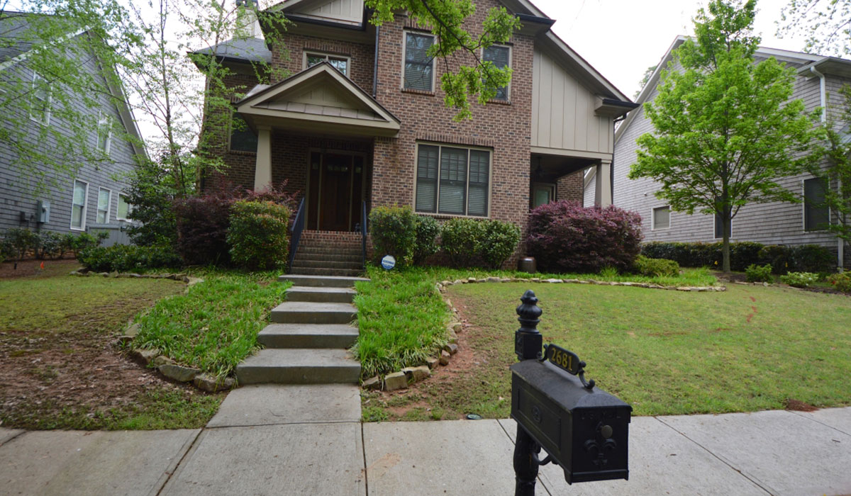 brick house with concrete stair walkway and black mailbox in the front yard