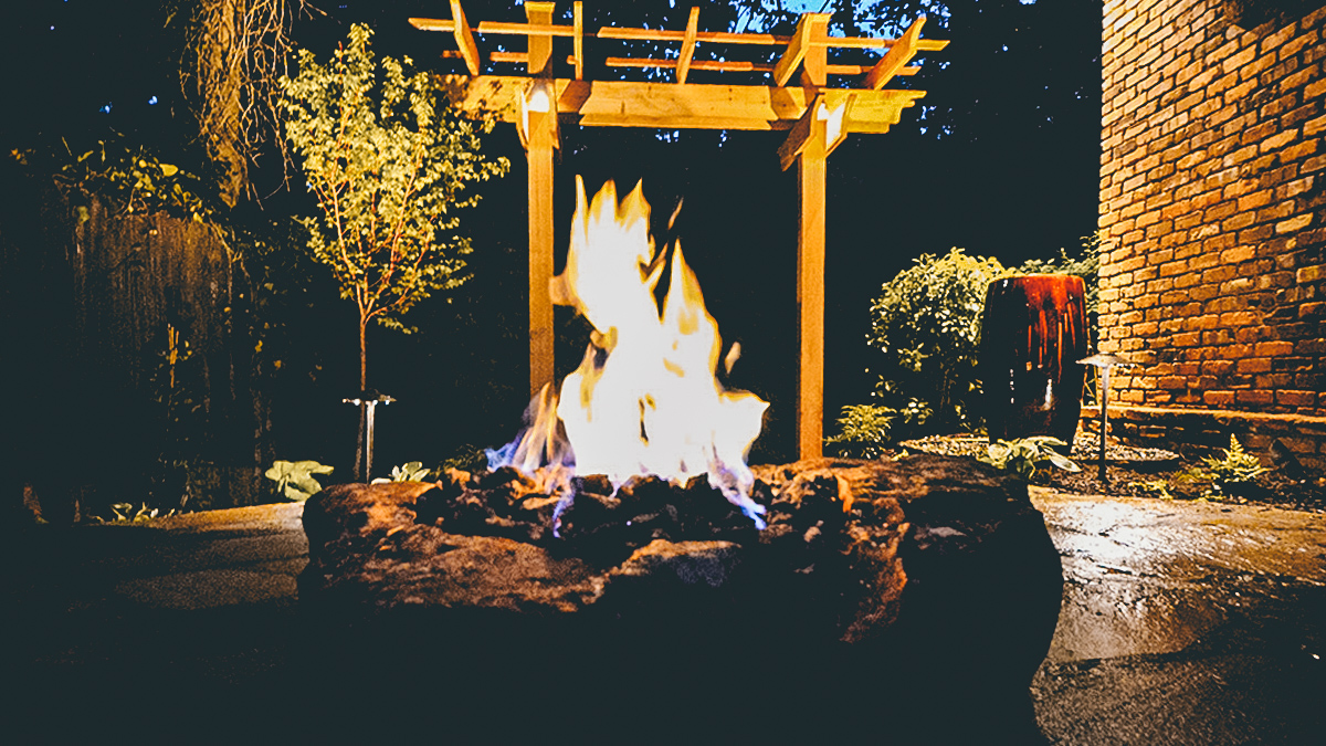 fire burning in stone fire pit in front of wooden backyard arbor