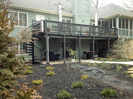 backyard deck with spiral stair case leading down to backyard with mulch and softscaping