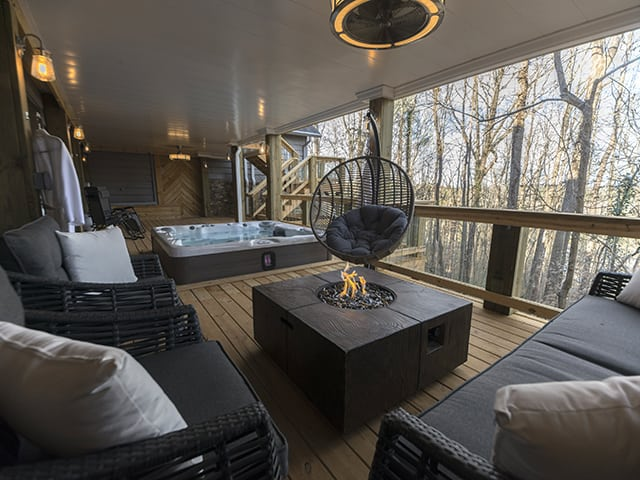 wooden patio with hot tub, outdoor cushion furniture, and designer fire pit