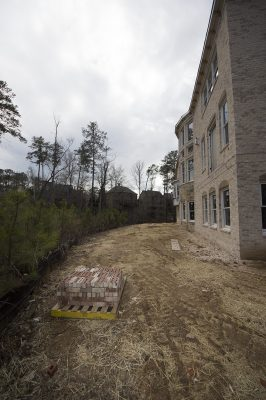 backyard landscape construction for erosion prevention of new brick house