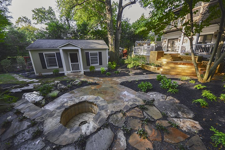 backyard guest house next to stone fire pit and wooden deck with designer outdoor landscaping