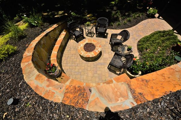 looking down on circular fire pit with hardscape design and outdoor furniture