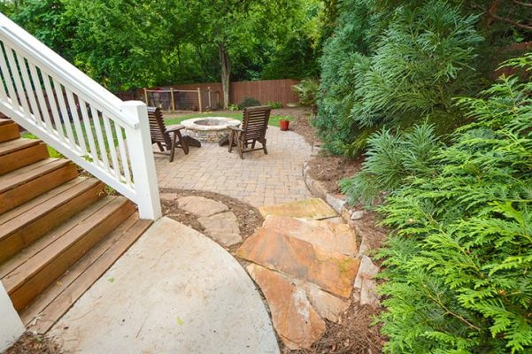 wooden and stone stairways leading down to backyard patio with chairs and stone fire pit